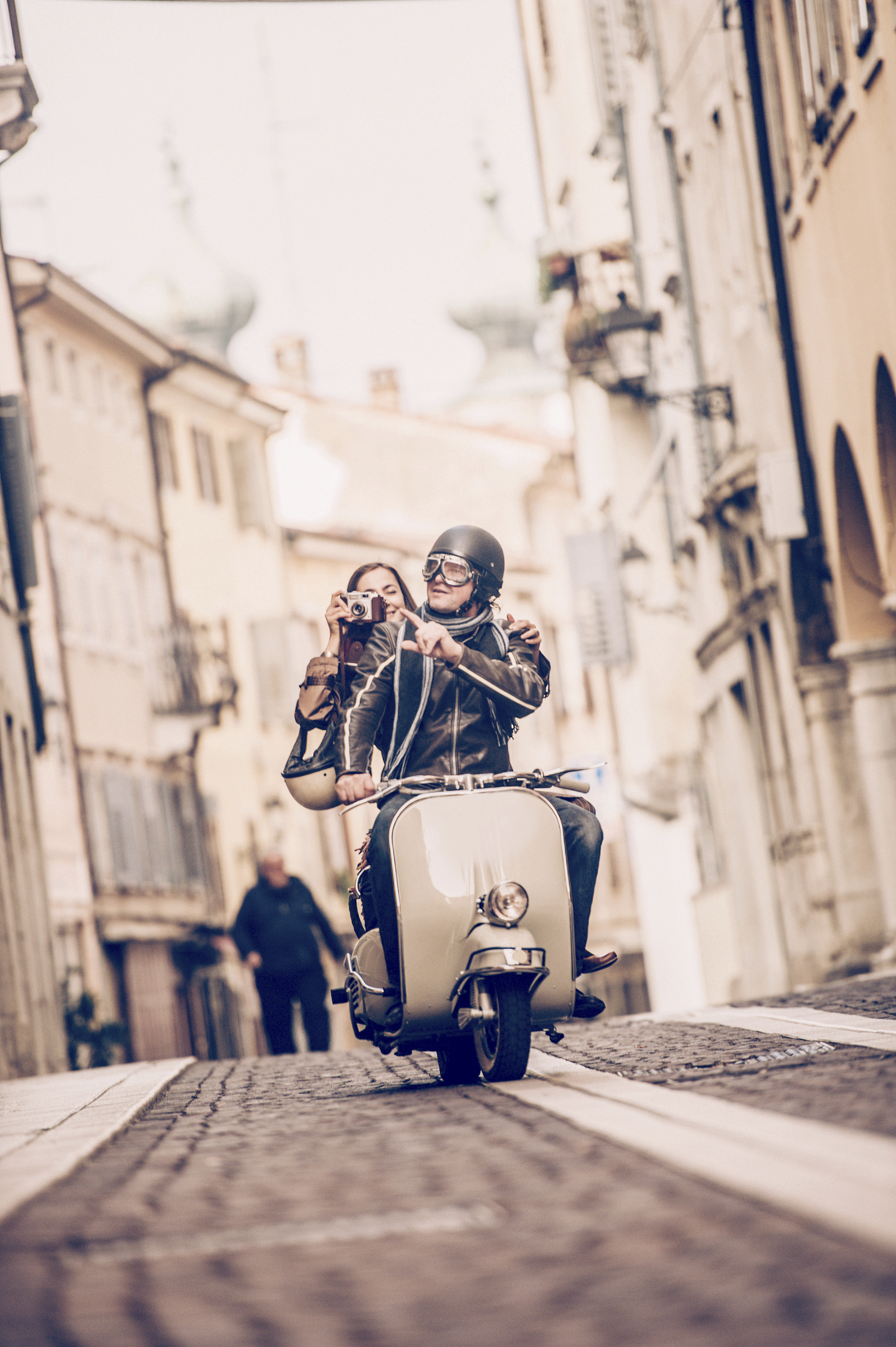 Vintage couple riding Vespa scooter in Italy, woman taking photos, front view