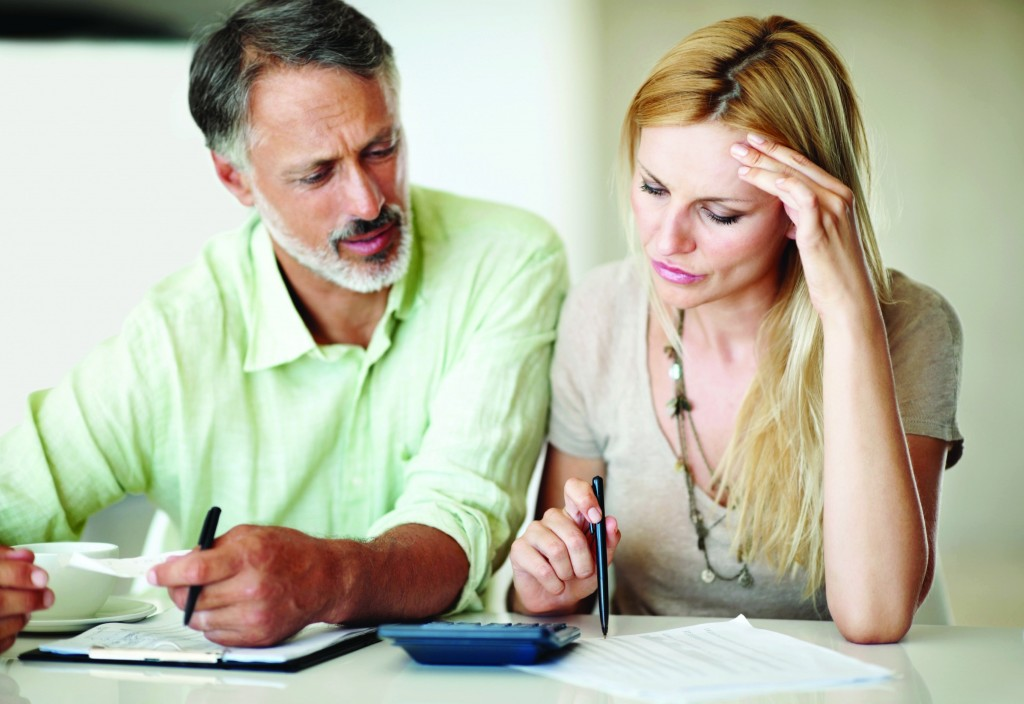 Tensed Caucasian woman and man calculating home finances