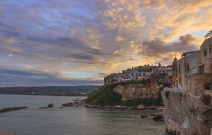 View of the historic center of Vieste at sunset during a summer evening.