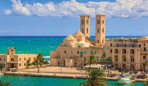View of Molfetta old town: the harbor and the Old Cathedral of St. Conrad (Duomo Vecchio of San Corrado).ITALY(Apulia).Old Cathedral of Molfetta in Romanesque style:church with three domes aligned with side half-barrels.