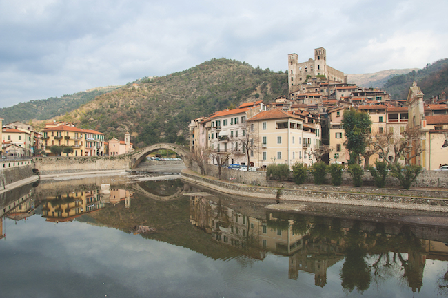 View of Dolceacqua medieval village. The famous roman humpback bridge and Doria castle reflecting in Nervia river